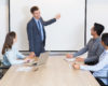 Young Caucasian business coach or leader consulting business team at seminar. Businessman standing and pointing at projection screen. Multiethnic businesspeople sitting ta table and looking at him